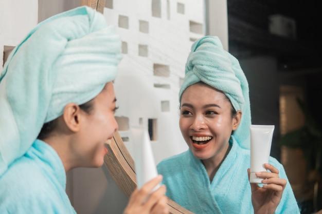 フェイシャルトリートメントクリームを保持している新鮮な肌を持つアジアの女性