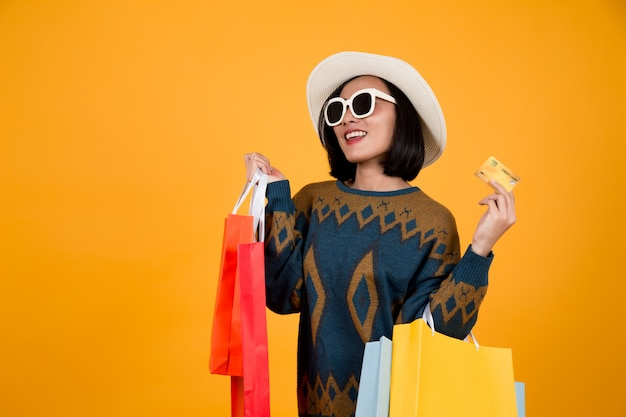 Asian woman with glasses holding colorful paper bags and a credit card