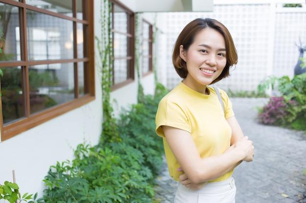 황금빛 짧은 머리를 한 아시아 여성은 짧은 소매 티셔츠 노란색과 크림색 바지를 입는다