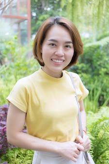 彼女が立っている間、金色の短い髪のアジアの女性は半袖のtシャツの黄色を着ています