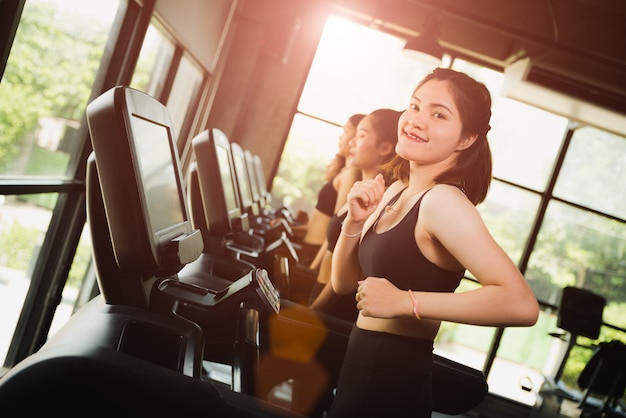 Asian woman with group of young people running or jogging on treadmills