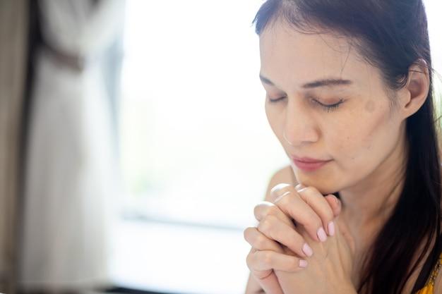 손으로 기도하는 아시아 여성, 침대에서 손을 접고 기도합니다. 믿음, 영성 및 종교에 대한 개념입니다.