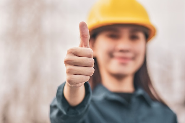 Asian woman with hard hat showing thumb up