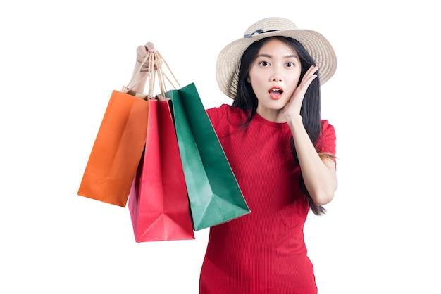 白い背景で隔離の買い物袋を運ぶ帽子を持つアジアの女性