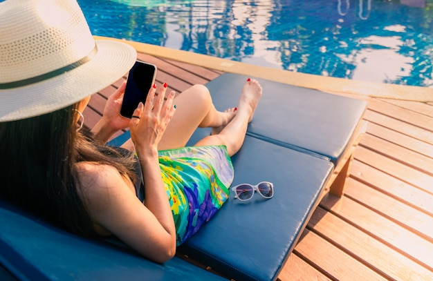 Asian woman with hat and swimsuit sit on sunbed at poolside and using smartphone on summer vacation by swimming pool.