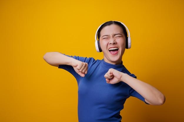 Азиатская женщина с наушниками, слушая музыку, танцует на желтом.
