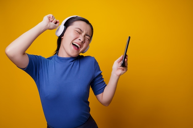 Азиатская женщина с наушниками, слушая музыку со смартфона на желтом.