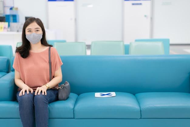病院のレジカウンターの前に立っている衛生フェイスマスクとアジアの女性