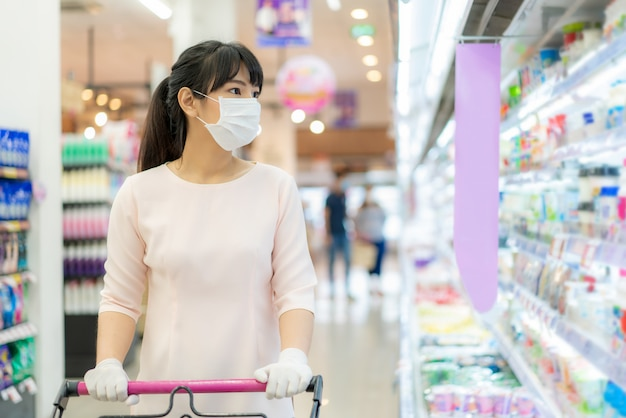 Asian woman with hygienic mask and rubber glove with shopping cart in grocery and looking for yogurt or daily fresh milk to buy during covid-19 outbreak for preparation for a pandemic quarantine
