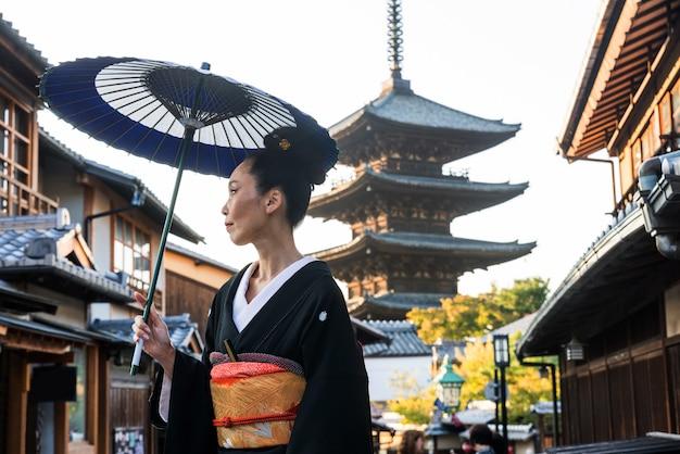 Азиатская женщина с кимоно, идущей на пагоде ясака в киото