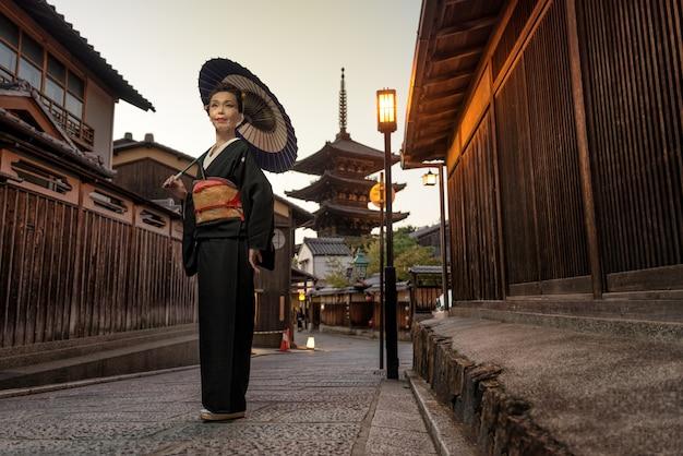 Азиатская женщина с кимоно, идущим на пагоде ясака в киото