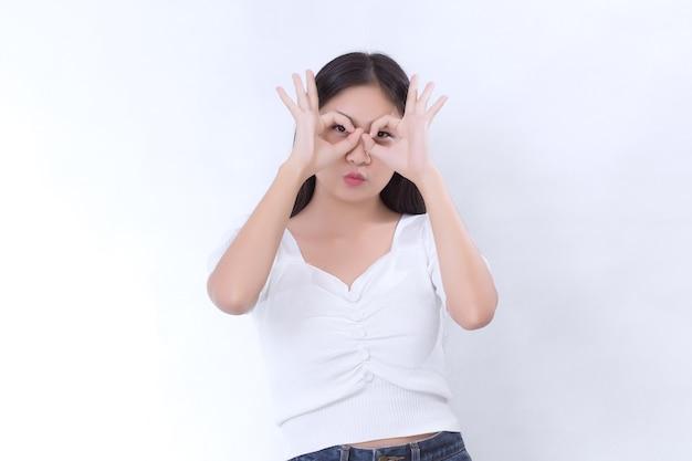 長い黒髪のアジアの女性は白いシャツを着て、白い背景に手の「オーケー」サインを示しています。