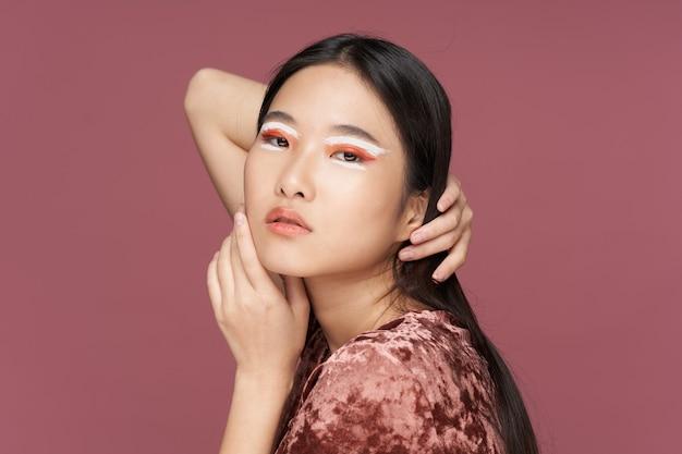 彼女の顔に化粧をしているアジアの女性は、トリミングされた彼女の頭の髪をまっすぐにします。高品質の写真