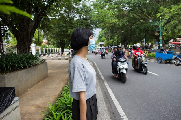道路を横断する医療マスクを持つアジアの女性