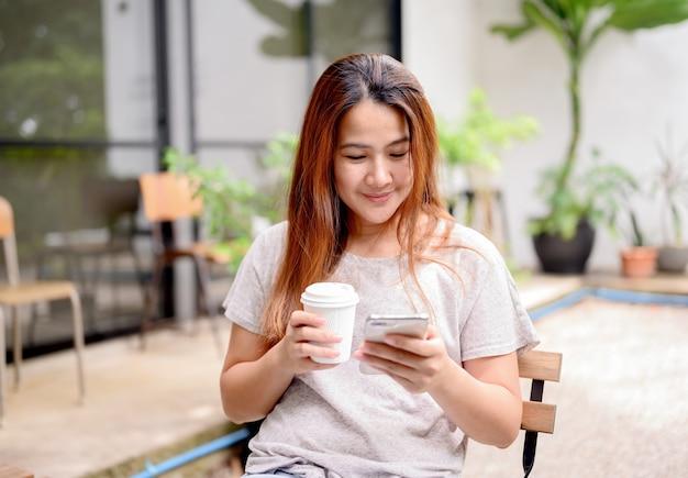 携帯電話とコーヒーだけでアジアの女性。休日には植物園でリラックスしてレクリエーションを楽しめます。