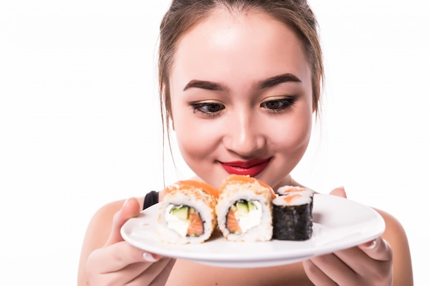 Asian woman with modest hairdo sits on the table eat sushi rolls smiling