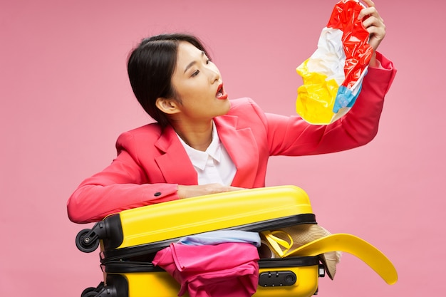 Asian woman with open suitcase in her hands