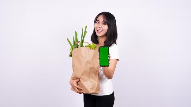 신선한 야채 종이 봉지와 격리 된 흰색 표면에 녹색 스크린 전화를 들고 아시아 여자