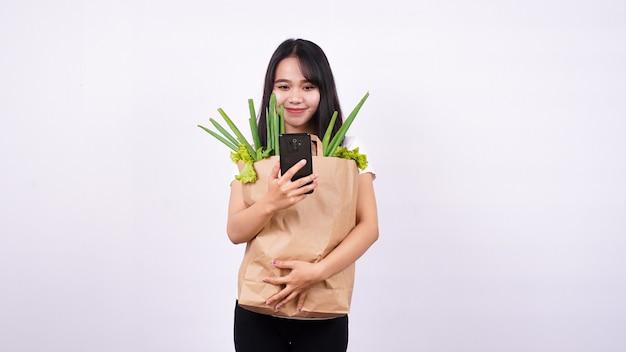 신선한 야채 종이 봉지와 격리 된 흰색 표면에 전화를 들고 아시아 여자