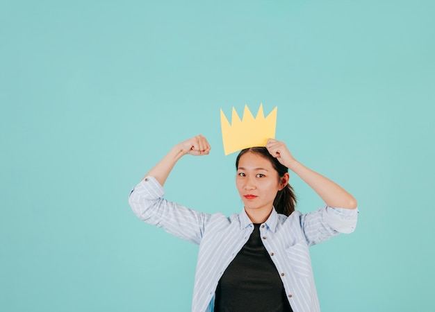 Asian woman with paper crown showing muscles