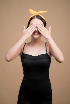 ピンナップメイクのアジアの女性は手で目を覆います。
