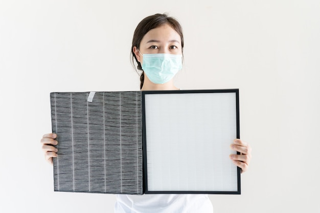Asian woman with protective hygiene face mask changing a hepa air purifier filter