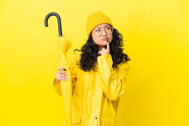 見上げている間疑いを持っている黄色の背景に分離された防雨コートと傘を持つアジアの女性
