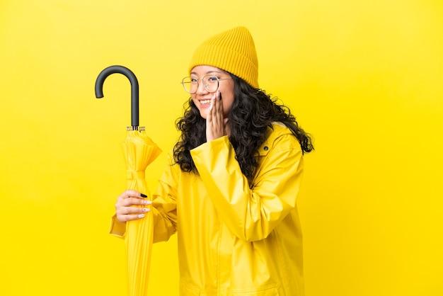 黄色の背景に分離された防雨コートと傘を持つアジアの女性は、口を大きく開いて叫んでいます