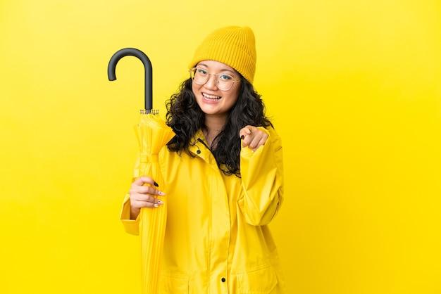 Азиатская женщина с непромокаемым пальто и зонтиком, изолированными на желтом фоне, удивлена и указывает вперед