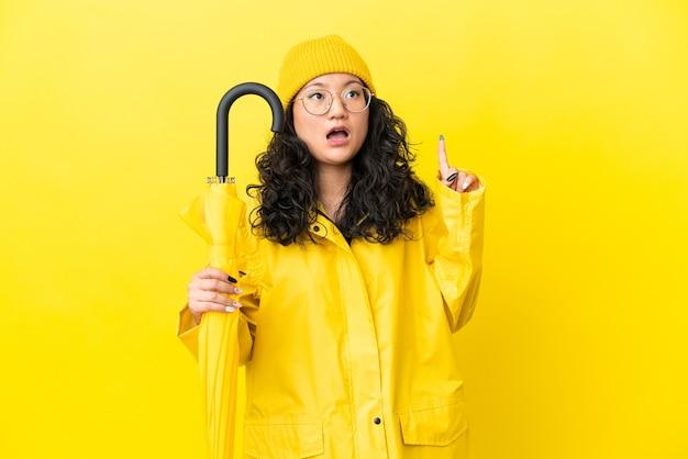 指を上に向けるアイデアを考えて黄色の背景に分離された防雨コートと傘を持つアジアの女性