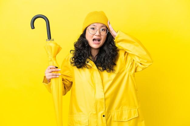 Азиатская женщина с непромокаемым пальто и зонтиком изолирована на желтом фоне с удивленным выражением лица