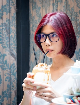 Asian woman with red hair is drinking coffee in vintage cafe