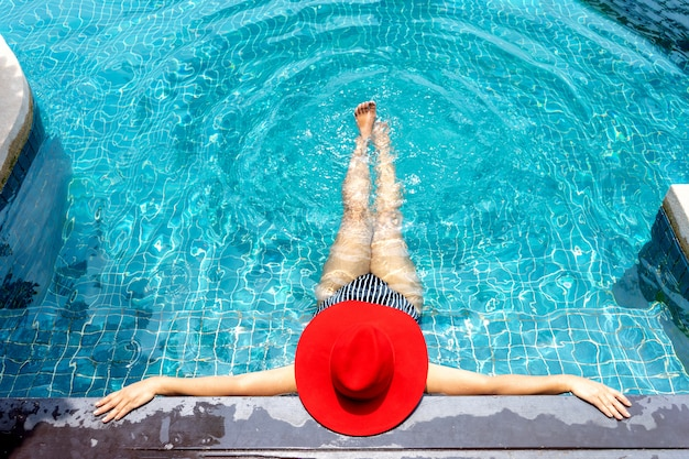 Asian woman with red hat relax on swimming pool.