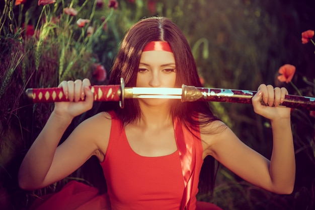 Asian woman with samurai sword on the nature