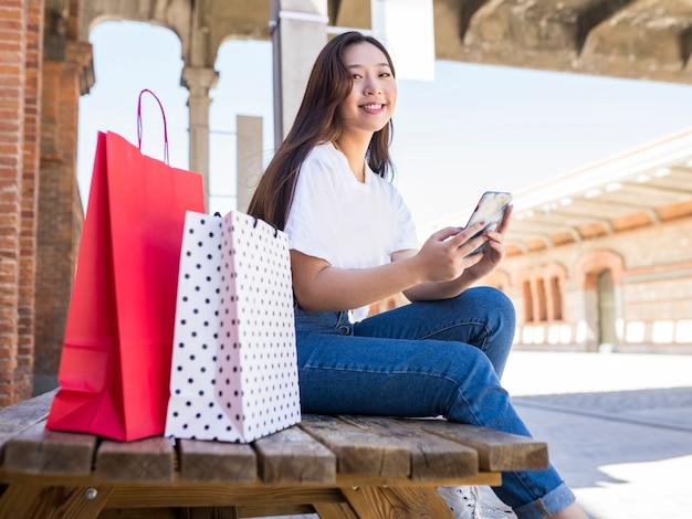 쇼핑 가방과 마을 주변 전화 아시아 여자