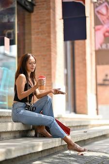 行く買い物袋レトロなカメラコーヒーと階段に座って手にスマートフォンを持つアジアの女性