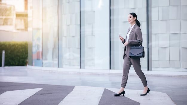 通りにぼやけている建物の背景にスマートフォンの立っているとアジアの女性。