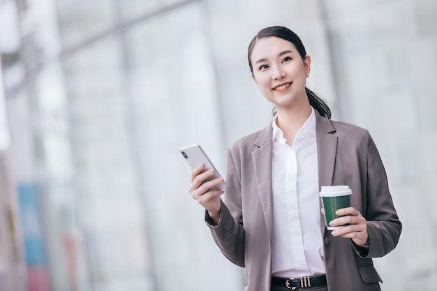Азиатская женщина с смартфоном, стоящим на фоне запачканной улицы.