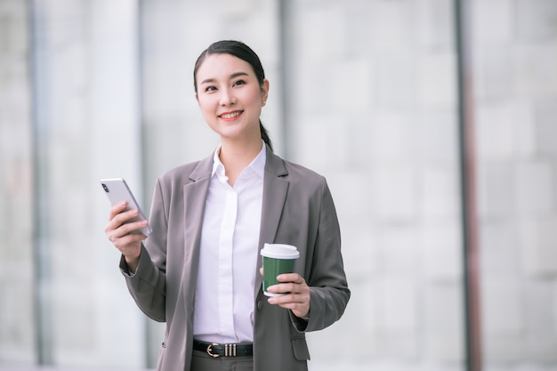 Asian woman with smartphone standing against street blurred building. fashion business photo of beautiful girl in casual suite with phone and cup of coffee.