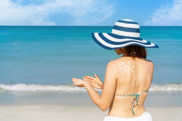肩に太陽の形をしたアジアの女性は、彼女の手に日焼け止めクリームを塗ります。ビーチのコンセプトの夏。