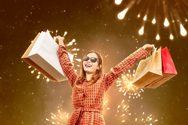 Asian woman with sunglasses carrying a shopping bag with fireworks background