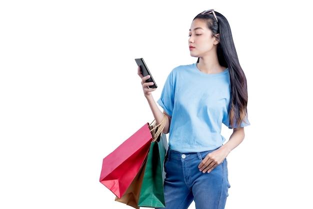 白い壁に隔離された携帯電話を保持している買い物袋を運ぶサングラスとアジアの女性