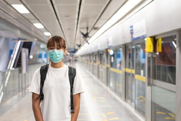 Азиатская женщина с хирургической маской для лица чувствует себя уставшей, используя смартфон, стоя в ожидании метро, надземного метро, переноски рюкзака, путешествия в город, социальное дистанцирование, коронавирус, covid19
