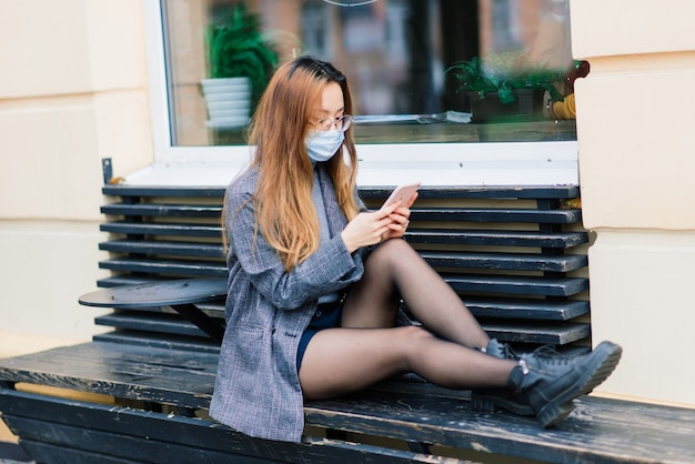 Asian woman with surgical mask, face protection in the city, cafe