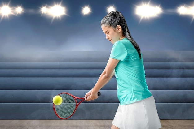 Asian woman with a tennis racket in her hands hit the ball