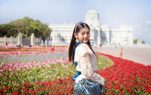 屋外庭園とランドマーク建築のモダンなタイスタイルのタイの伝統的なドレスとアジアの女性