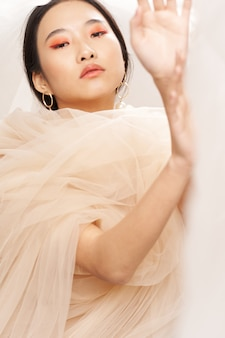 손 화장으로 몸짓하는 그녀의 어깨에 투명한 천을 가진 아시아 여성