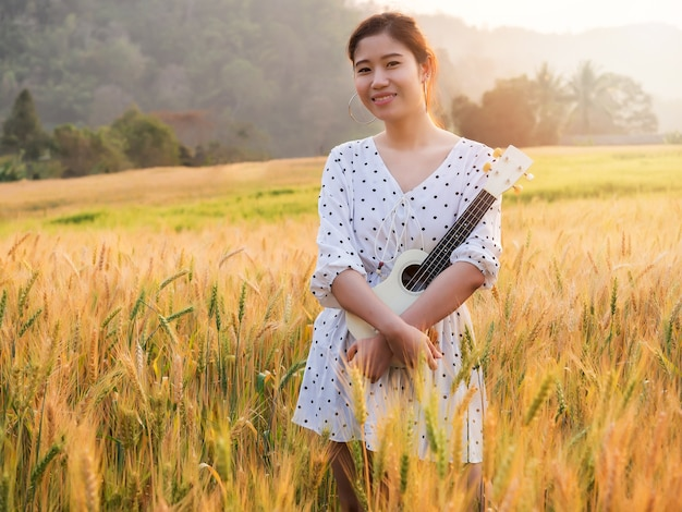 Asian woman with ukulele in barley field at sunset time.