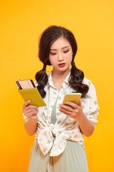 Азиатская женщина со старинной камерой счастлива и улыбается на желтом фоне