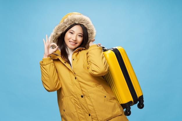파란색 배경에 노란색 가방을 든 아시아 여성과 따뜻한 재킷 여행 모델